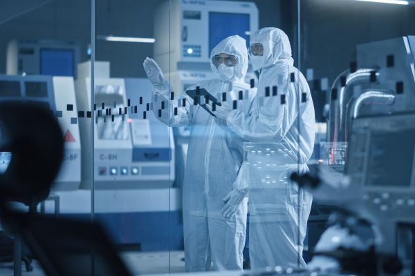 Factory Cleanroom: Engineer and Scientist Wearing Coveralls, Standing in Workshop Talk and Use Tablet Computer, Professionals Develop Technology for Modern CNC Machinery and Electronic Equipment